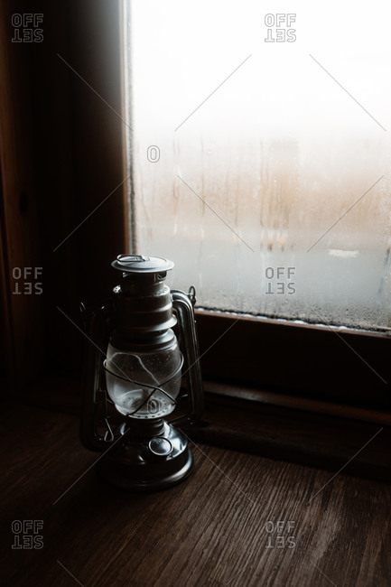 Cozy atmosphere of room with retro oil lantern placed on windowsill with misted window in house