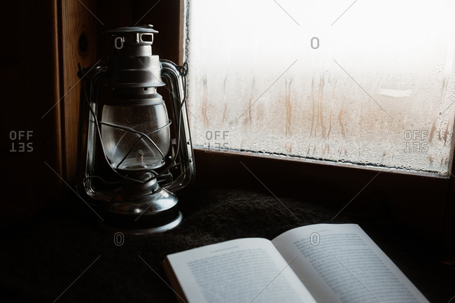 Cozy atmosphere of room with retro oil lantern and opened book placed on windowsill with misted window in house