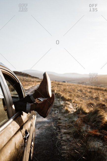 Unrecognizable tourist lying in car with legs out of window on background of sunrise in Scottish Highlands