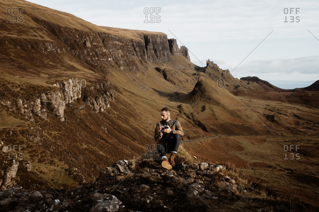 Male tourist with professional photo camera taking pictures and admiring wonderful mountains in Scottish Highlands in fall