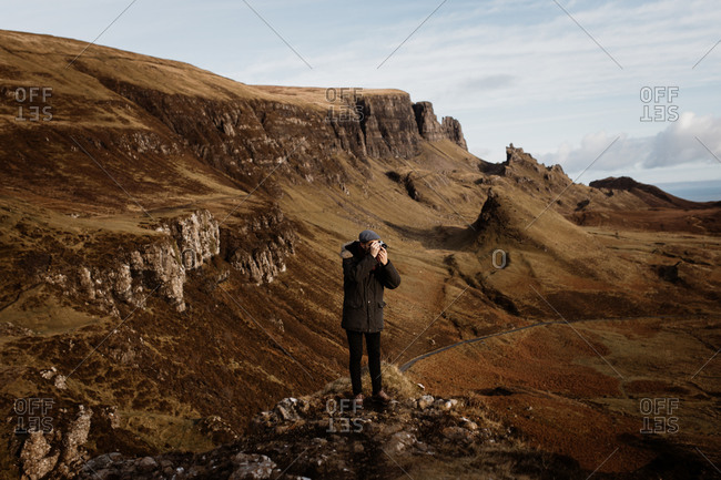 Anonymous male tourist with professional photo camera taking pictures of wonderful mountains in Scottish Highlands in fall