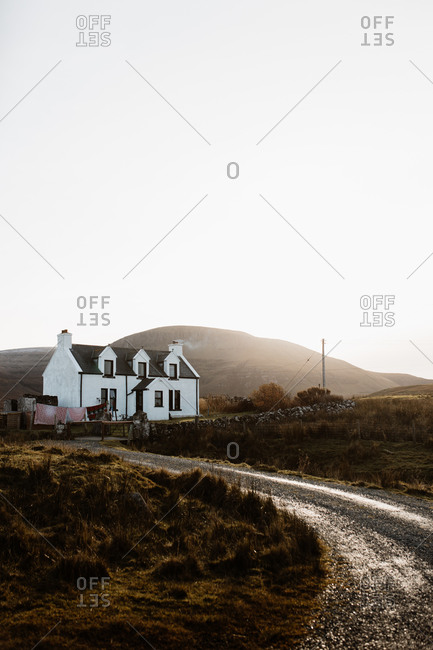 Rural road leading to solitary house located on background of wonderful mountainous landscape in Scottish Highlands in autumn
