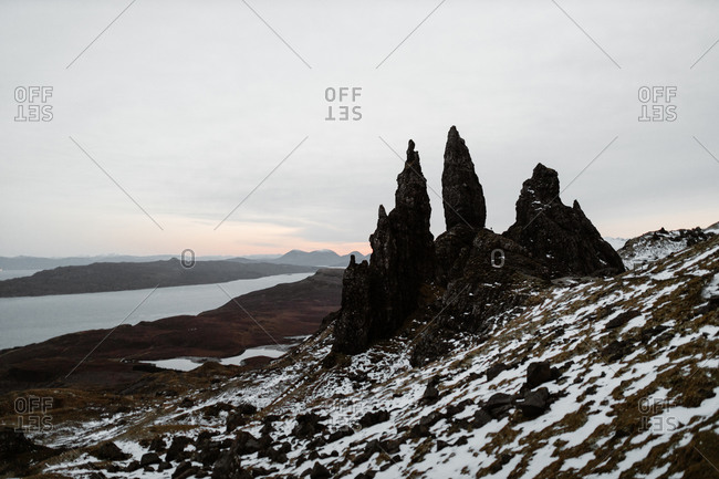 Old Man of Storr rock on slope covered with snow in winter on background of cloudy sky in Scottish Highlands