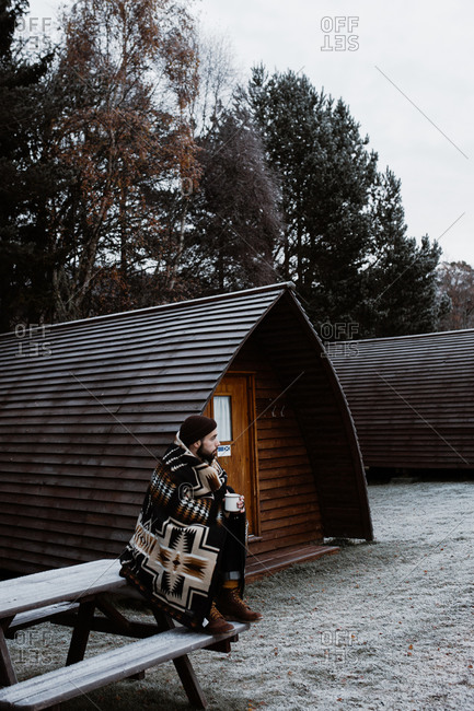 Side view of tranquil male tourist covered with blanket sitting on wooden bench near cottage and looking away while enjoying vacation in Scottish Highlands in winter