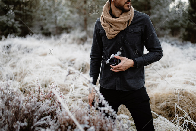 Cropped unrecognizable man with photo camera standing in meadow with frozen grass in winter in Scottish Highlands