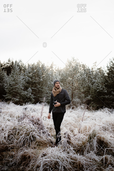 Man with photo camera standing in meadow with frozen grass in winter in Scottish Highlands looking away