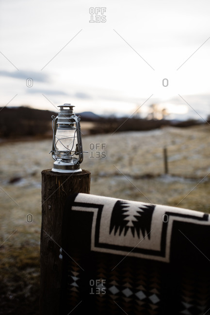 Vintage kerosene lamp placed on wooden fence in village on cloudy day in Scottish Highlands