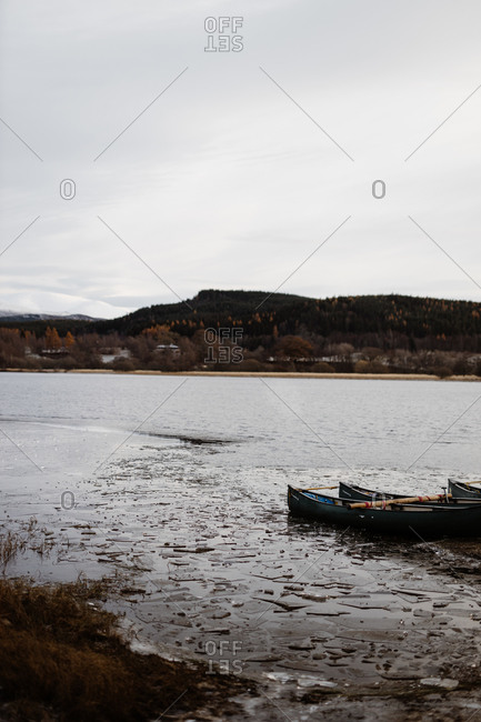 Lonely boat with paddle on shore near calm lake on background of mountainous landscape in Scottish Highlands