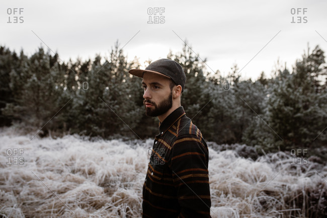 Man with hat standing in meadow with frozen grass in winter in Scottish Highlands looking away