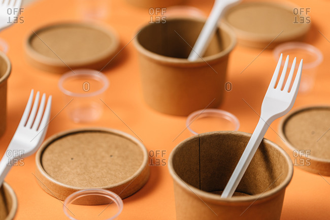 High angle of cardboard containers with plastic forks arranged with small plastic cups for takeaway food service on orange table