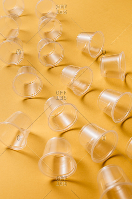 From above composition of small transparent disposable plastic cups for takeaway food service arranged on yellow background