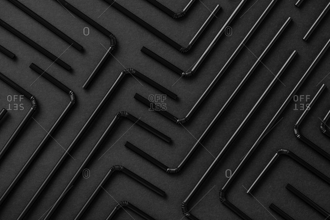 Top view flat lay composition with black plastic straws for takeaway drinks arranged in geometric ornament on black background
