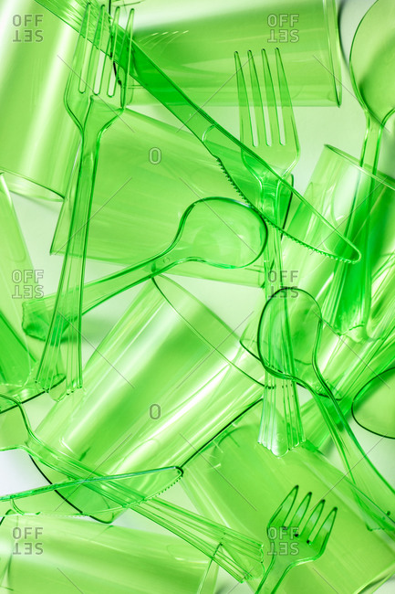 Top view composition of bright green transparent plastic cups with forks and spoons and knives placed on white background