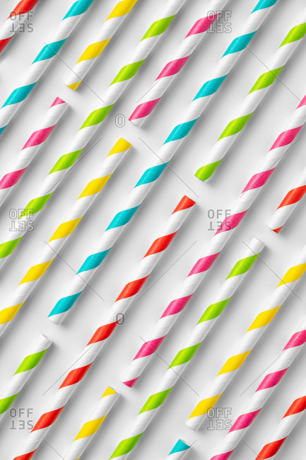Top view flat lay composition of multicolored striped plastic straws for drinks arranged on white background