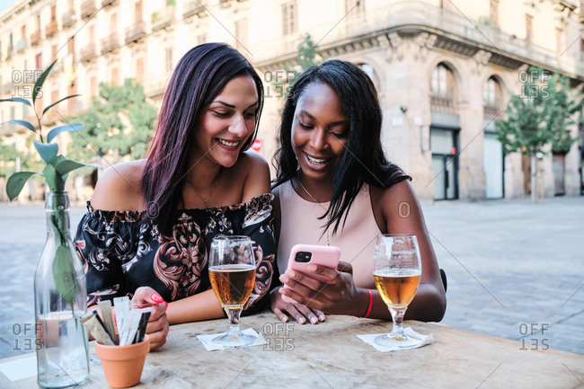 Positive multiracial women sitting at table in outdoors cafe and chatting on social media via cellphones at weekend in city