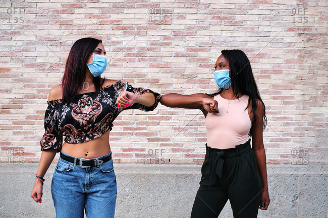 Multiethnic female friends wearing medical masks bumping elbows while greeting each other during coronavirus epidemic