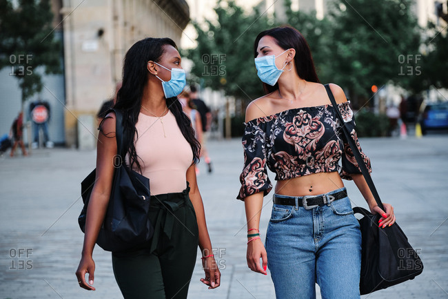 Multiracial female friends wearing medical masks walking along street and looking at each other during coronavirus pandemic