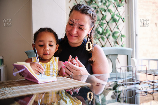 Multiethnic mother and little daughter sitting at table at home and writing in notebook while studying at home
