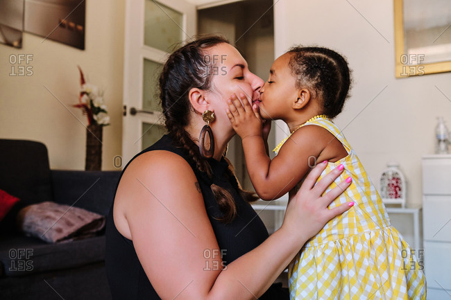Side view of multiracial delighted woman and little girl cuddling tenderly and kissing while sitting on floor in living room