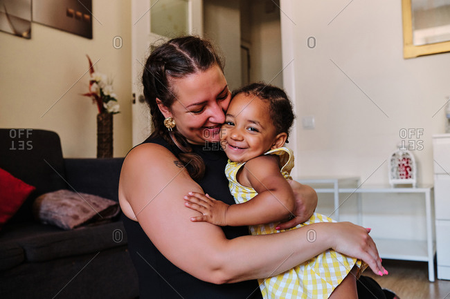 Side view of multiracial delighted woman and little girl cuddling tenderly while sitting on floor in living room