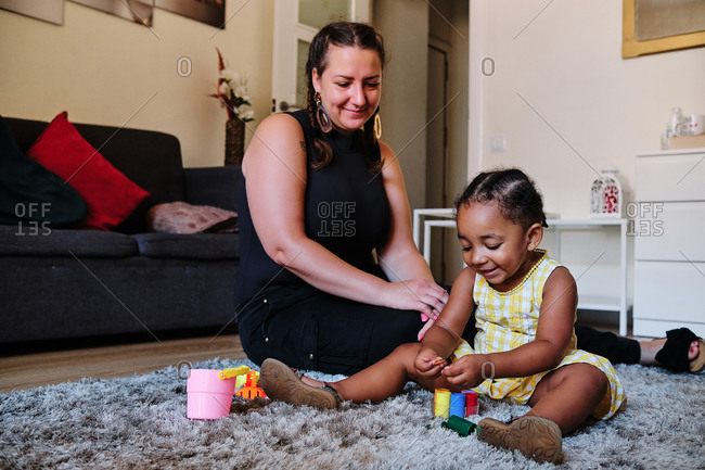 Content woman and African American little girl sitting on floor in coy living room and playing with toys while enjoying weekend together