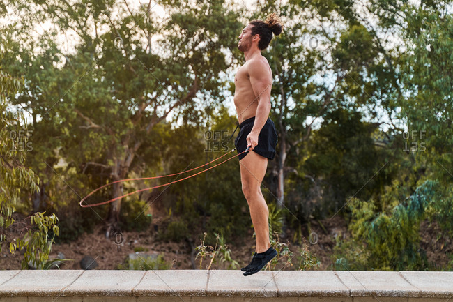 Side view of active male athlete with naked torso jumping rope during cardio training in park