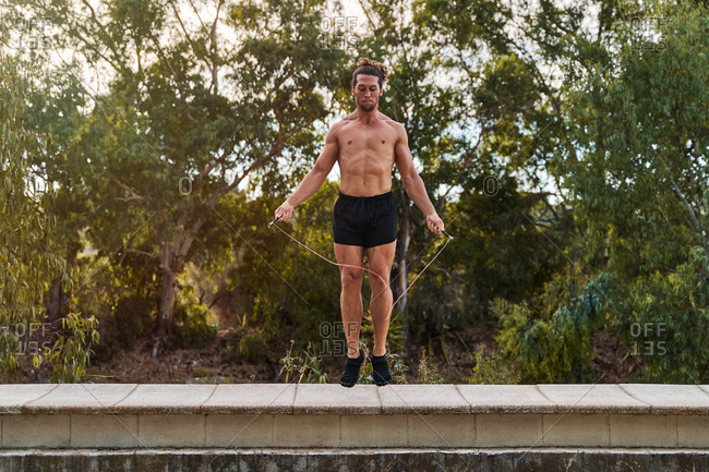 Active male athlete with naked torso jumping rope during cardio training in park