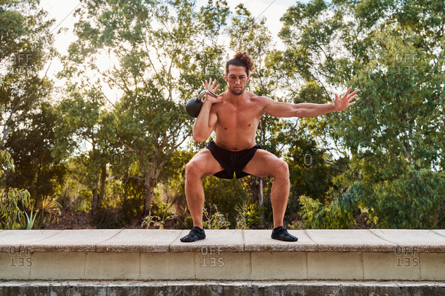 Strong sportsman doing squats with heavy kettlebell during functional training in city