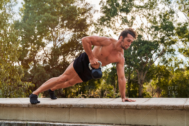 Athletic male with naked torso standing in plank and touching kettlebell during workout