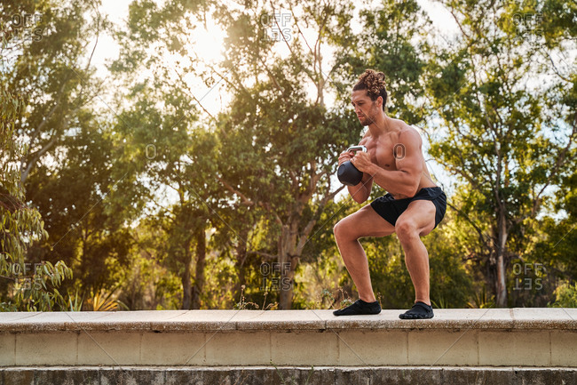 Side view of strong sportsman doing squats with heavy kettlebell during functional training in city