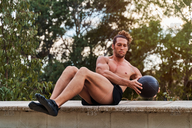 Concentrated male athlete with strong naked torso balancing with medicine ball while doing abdomen exercises during training in park