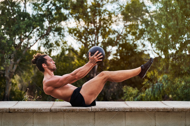 Side view of concentrated male athlete with strong naked torso balancing with medicine ball while doing abdomen exercises during training in park