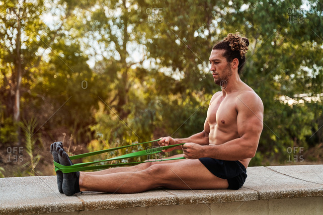 Side view of muscular sportsman sitting on stone border in park and stretching legs with resistance band before training