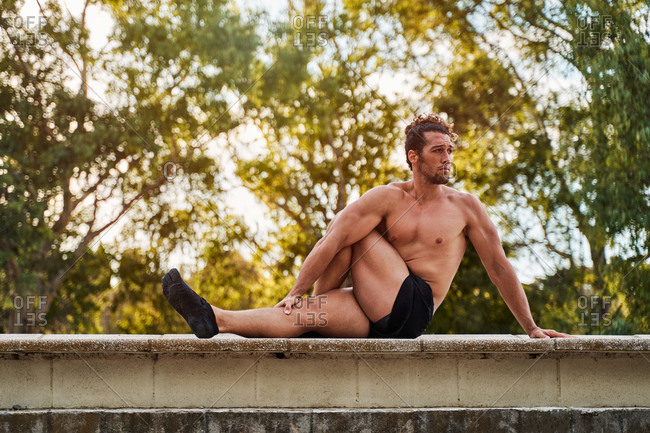 Side view of flexible male athlete sitting on stone border and doing forward bend while stretching body before training
