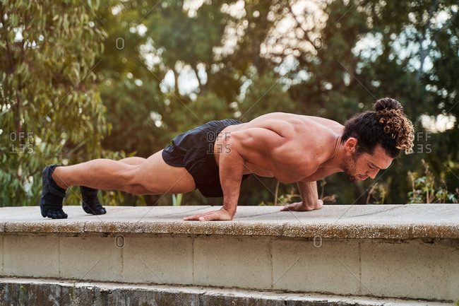 Full length of motivated strong fit male doing forearm plank exercise during intense abs training on paved square in city