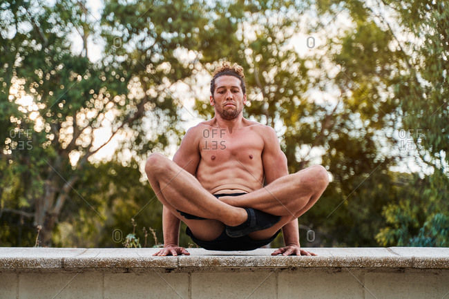 Peaceful male doing yoga in Padmasana in park in summer while balancing on hands and looking down