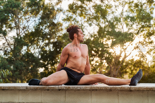 Side view of confident shirtless sportsman sitting on stone border in park and warming up legs while stretching before workout and looking away