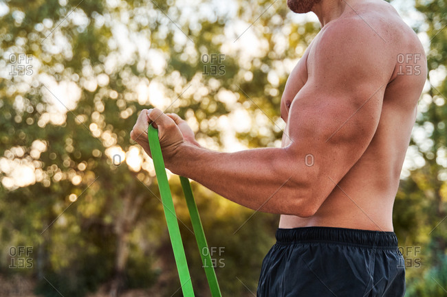 Side view of muscular male athlete pumping biceps while doing exercises with resistance band during workout in park