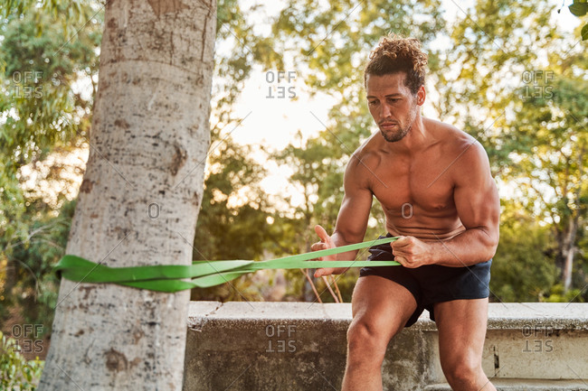 Muscular male athlete pumping biceps while doing exercises with resistance band during workout in park