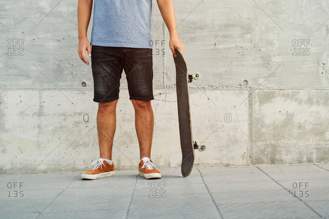 Unrecognizable crop male in street style outfit standing with skateboard near urban building in city