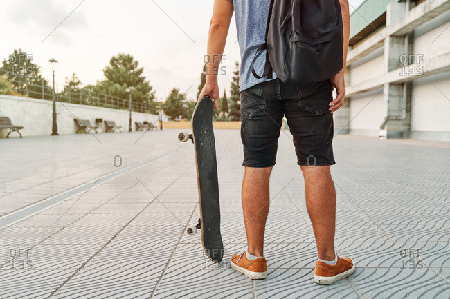Unrecognizable male in street style outfit standing with skateboard near urban building in city
