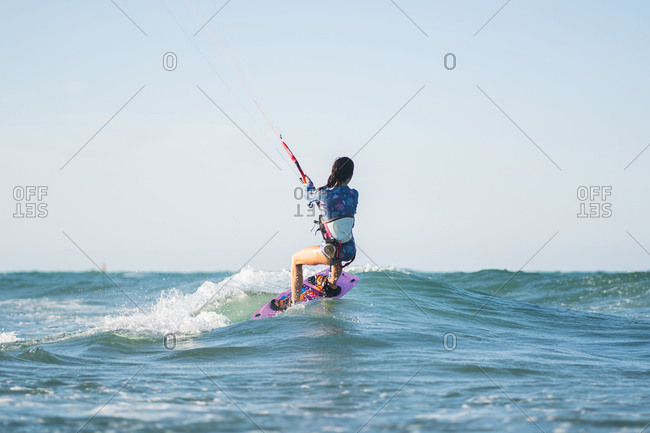 Back view of fit female kite surfer in swimsuit ridding waves in sea on sunny day in summer
