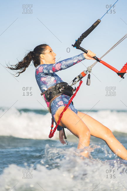 Side view of fit female kite surfer in swimsuit ridding waves in sea on sunny day in summer