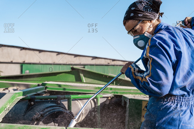 Employee in workwear and protective respirator cleaning agricultural machine in countryside on sunny day