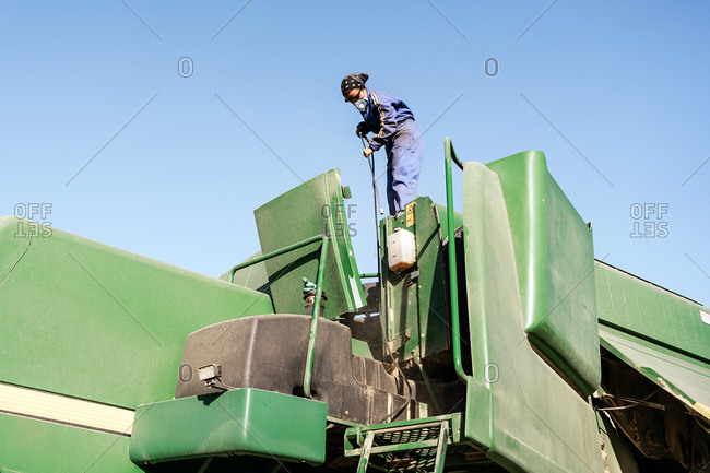Low angle of unrecognizable employee in workwear and protective respirator cleaning agricultural machine in countryside on sunny day