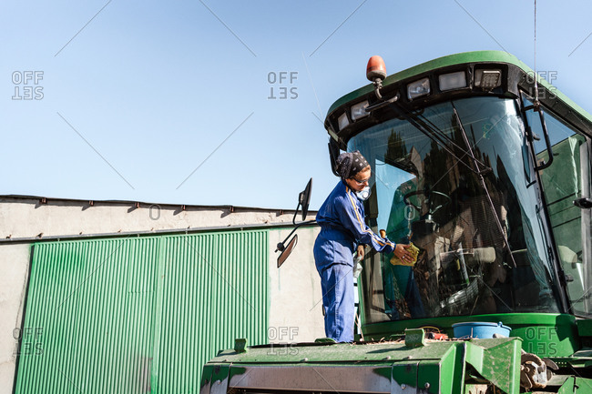 Side view low angle of busy female worker in uniform washing window of combine harvester parked in rural area