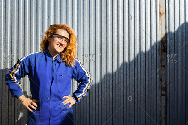 Cheerful female engineer in protective glasses and workwear standing near metal wall at plant and looking away while enjoying break during work