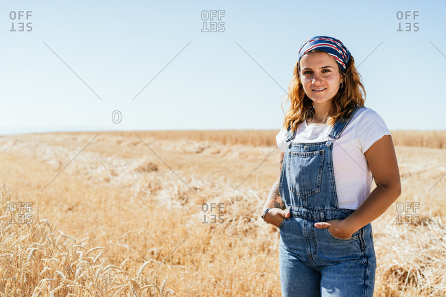 Female in denim overalls standing along wheat agricultural field and admiring amazing rural landscape in summer looking at camera