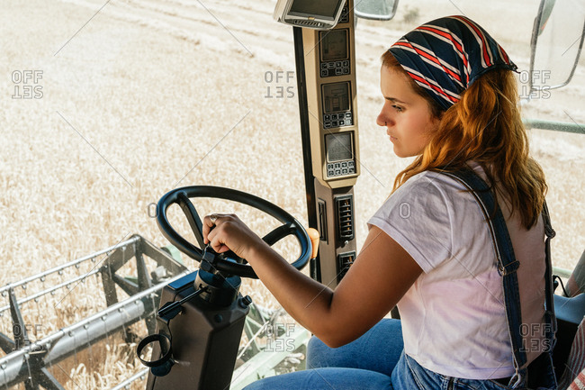 Side view of serious female farmer operating combine harvester and collecting wheat in field in rural area