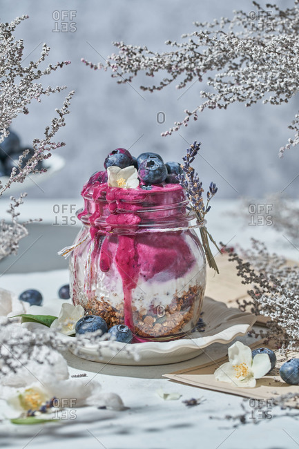 Glass jar with nutritious yogurt with healthy granola and fresh blueberries placed on table for breakfast in morning